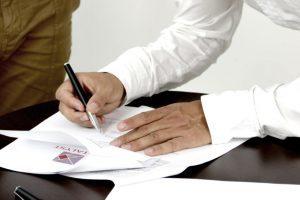 Mann schreibt auf ein Blatt Papier